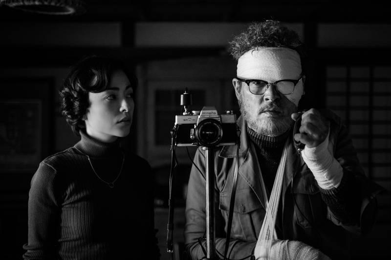 包帯姿でシャッターを切るジョニー・デップの姿 水俣を撮影した写真家役 「MINAMATA」場面写真